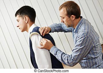 male tailor designer make marks on a jacket during bespoke suit fitting