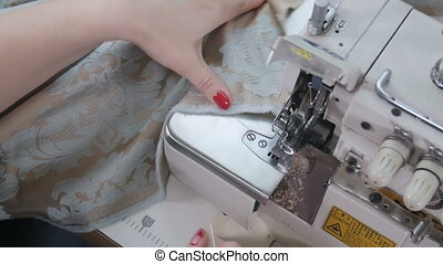Tailor using a cutter for cutting fabrics. Close up. Slow...