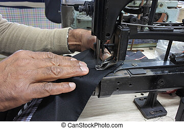 Tailor using buttonhole machine on fabric