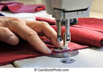 Tailor using sewing machine to stitch fabrics