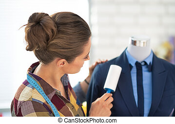 Tailor woman cleaning business suit. rear view