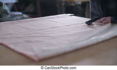 Tailor working at studio cutting fabric, detail of hand with scissors