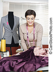 Tailor Working At Table By Mannequin In Factory