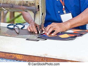 Tailor working on a vintage sewing machine.
