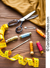Tailoring. Tape measure and colorful thread on dark wooden background, flat lay.