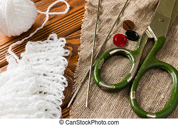 tailors scissors on fabric next to a ball of yarn