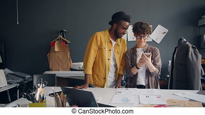 Pair of tailors African American man and Caucasian woman are taking photo of flat lay shooting sketches with smartphone camera then watching photographs talking