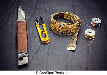 tailor's tools on a black background