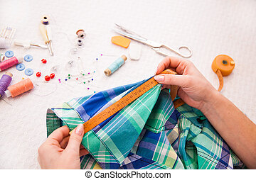 Tailor's working in a workroom measuring a garment
