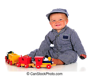 A chubby baby boy in striped coveralls and hat happily playing with a colorful woode train.