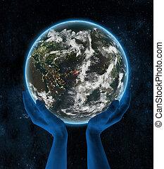 Tajikistan on night planet Earth in hands