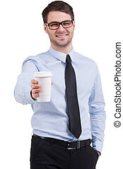 Take a break. Cheerful young man in shirt and tie stretching out a cup of coffee while standing isolated on white