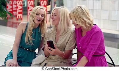Chicks taking break from shopping rush surfing the net