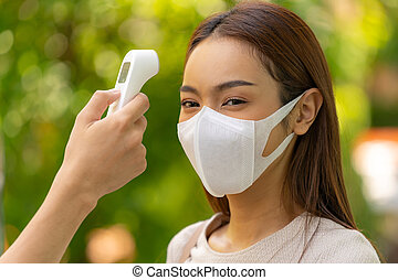 Take Temperature asian woman with face mask before getting in building for new normal lifestyle after coronavirus covid-19 pandemic. New normal healthy lifestyle concept.