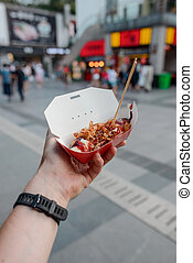 Take away food in hand on street background
