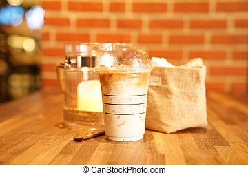 Take away Latte with Brick background on the wood table