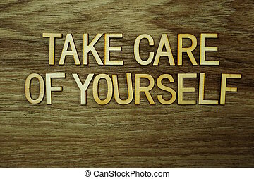 Take care Of Yourself text message on wooden background