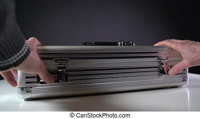 Take dollar bills from a metal suitcase. Close-up