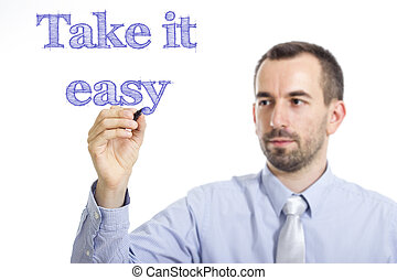 Take it easy - Young businessman writing blue text on transparent surface