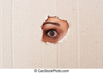 Take me out of here! Close-up of human eye looking through a hole in a cardboard