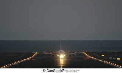 Take off at dawn - A frontal shot of a lighted runway and an...