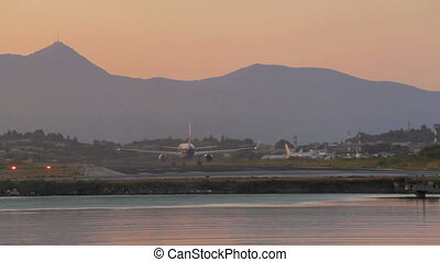 Take-off of airplane in Corfu airport during sunset, Greece....