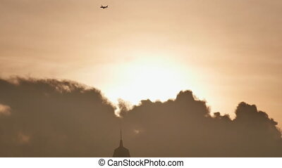 Take off the plane in the distance against the background of sunrise or sunset. Silhouette of an airplane. Airplane in the sky at sunset.