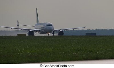 Takeoff run of an airliner. Aircraft takes off from runway on hazy summer day