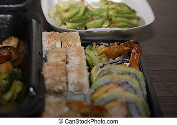 Takeout - Sushi and avocado slices plated in takeout boxes