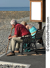 Elderly man holding a walking stick with a woman sitting together on a bench at the beach, with a sign in view, suitable for text.