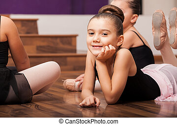 Beautiful little dance student laying on the floor and taking a break in dance class