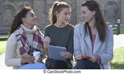 Taking a break - Three female friends sitting on a wall...