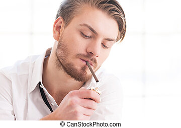 Taking a break to smoke. Handsome young man in shirt and tie lighting a cigarette