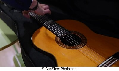 Taking a classical spanish acoustic guitar - Close-up of...
