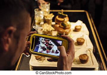 Man is taking a photo of his meal in a restaurant using his smart phone.