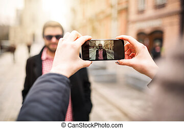 Taking a photo of young man