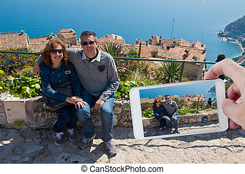 A couple of tourists in Eze, Cote d'Azur, photographed with a smartphone