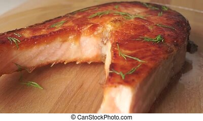 Taking a piece of freshly cooked salmon steak with a fork...