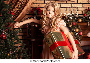 taking a present - Cute little girl standing with a gift at...