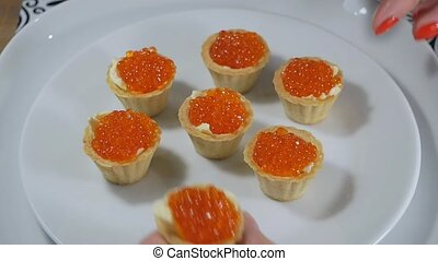 Taking a tartlet snack with red caviar and butter