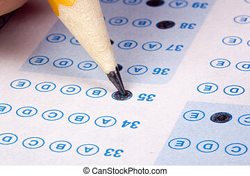 Taking a Test - Student filling out answers to a test with a...