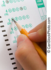 Female hand filling in a multiple choice examination answer sheet with a yellow pencil, focus on the tip of pencil
