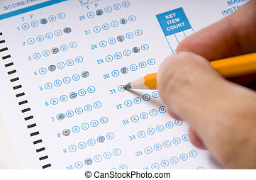 A hand holding a yellow pencil filling in a computer checked answer sheet on an examination. Education concept