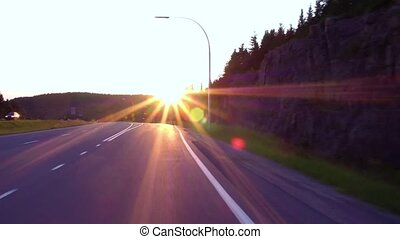 Taking an exit on the highway at sunset, with the sun straight in front of the car while exiting (driving in northern Quebec, Canada)