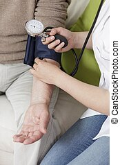 Taking blood pressure - Young woman using blood pressure...