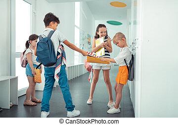 Rude dark-haired boy taking book away from little girl