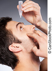 Taking care of his eyes. Side view of young man applying eye drops while standing against grey background