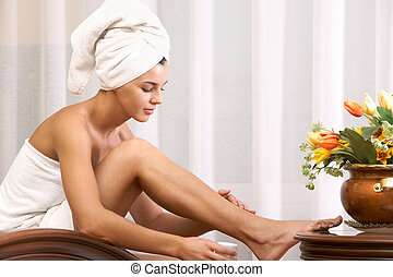 Portrait of pretty female taking care of her legs after bath