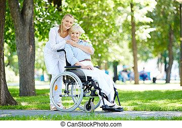 Taking care of patient - Pretty nurse taking care of senior...