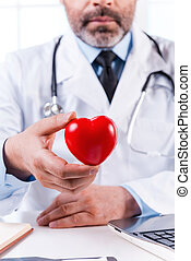 Taking care of your heart. Mature grey hair doctor holding heart shape toy and looking at camera while sitting at his working place